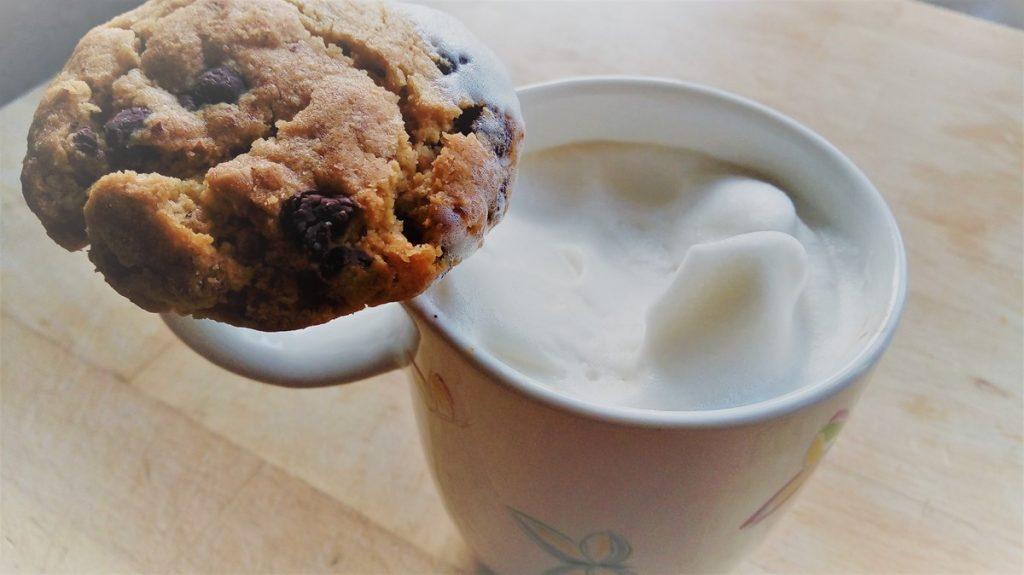 Eine Tasse Cappucino mit viel Sojamilch-Schaum. Ein Keks liegt auf dem Henkel und hat schon einen Schaumbart.