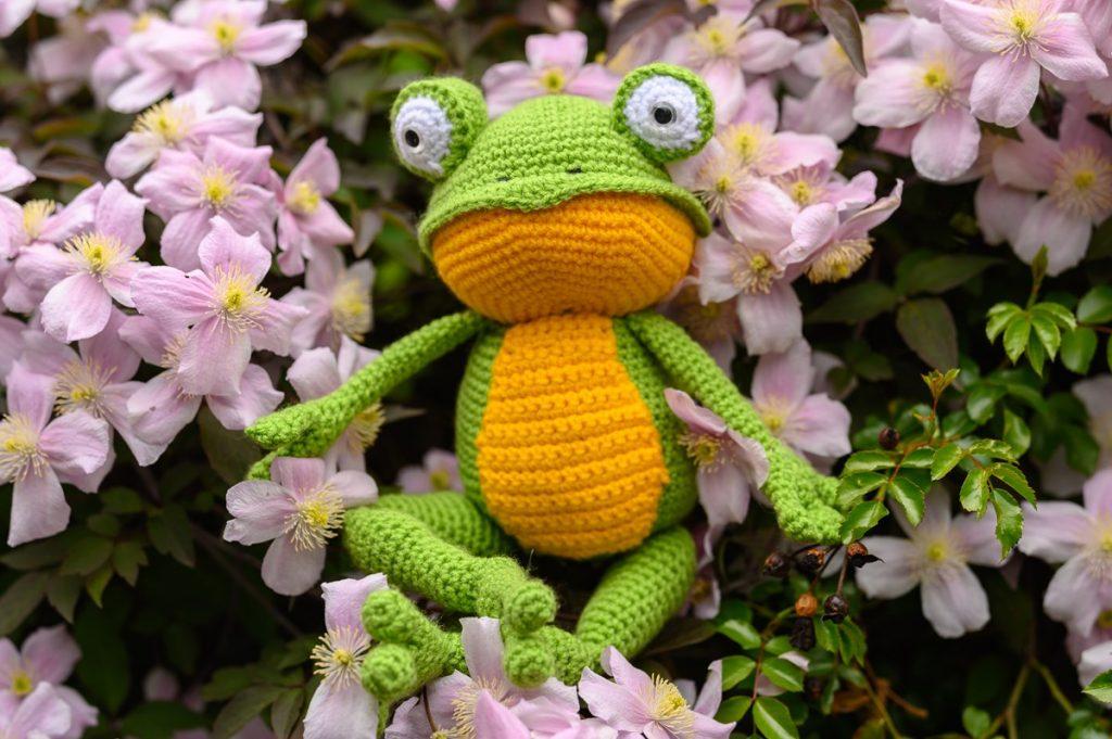 Amgurumi green-yellow frog in pink clematis