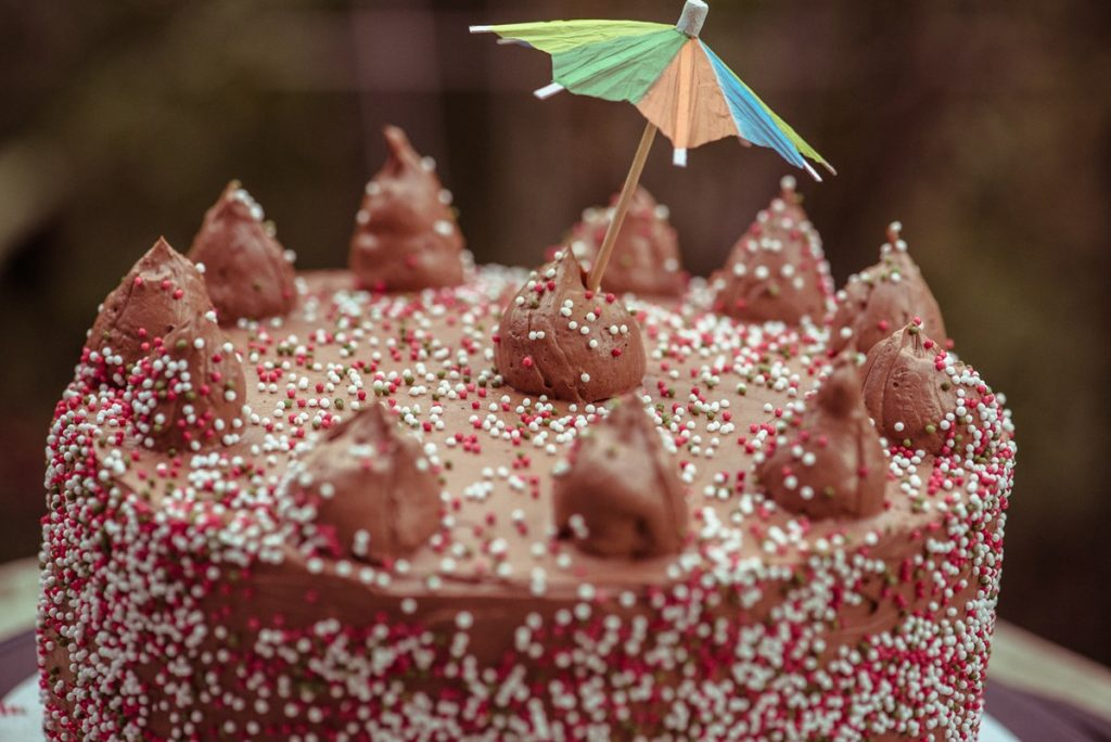 Chocolate cake covered with chocolate fudge frosting and poofs on top.