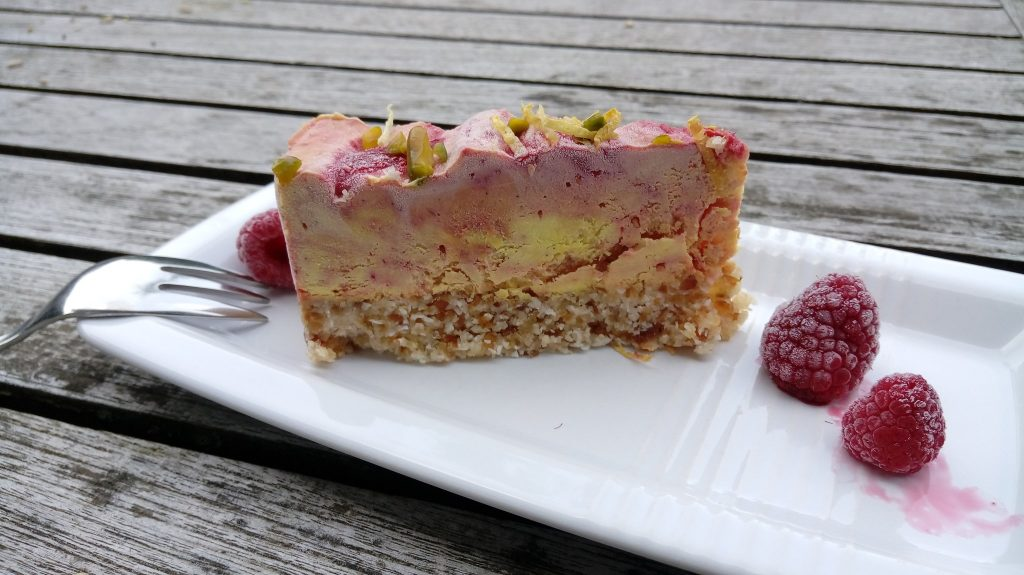 Slice of frozen raspberry lemon cashew cheesecake with raspberries on the plate